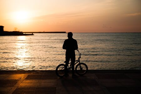 silhouette of young male with bicycle in city on sea sunset evening Stok Fotoğraf