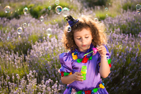 beautiful little girl in fairy purple costume with hat inflate soap bubbles outdoors Banque d'images - 111093196