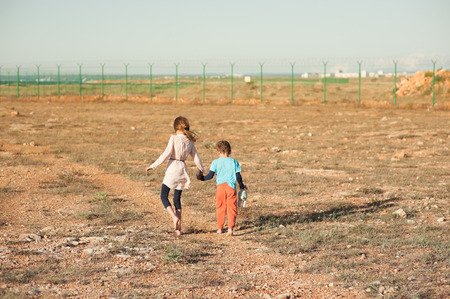 poor barefoot small girl and boy refugees walk in desert towards fencing with barbed wire