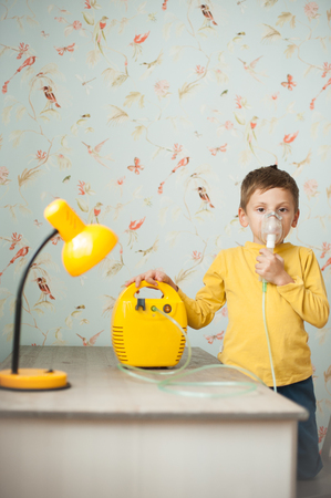 cute little sick caucasian child with device for inhalation in kids room inhale medicine