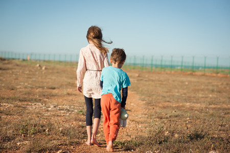 caucasian little boy and girl refugees walking alone in desert towards border with fence Stock Photo