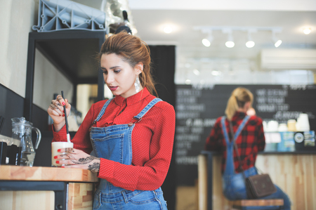 trendy young woman in red shirt and denim costume blending her coffee with straw in bar