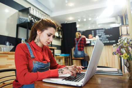 pretty modern young caucasian girl with henna tatoo working with laptop sitting in coffee bar