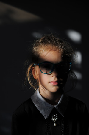 mysterious dark portrait mind concept of small caucasian girl in school dress and glasses