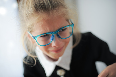 little caucasian girl in blue glasses and school black and white dress crying bitterly Reklamní fotografie