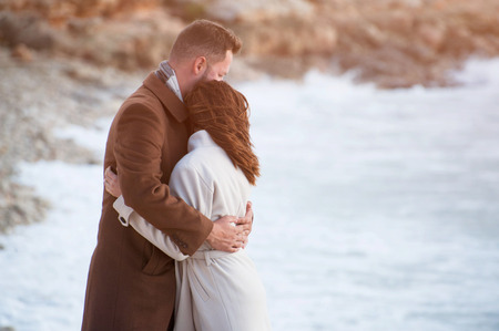 young trendy fashionable couple male and female in coat embrace near cold wind sea coast