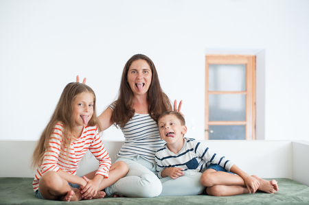 happy mother and two children showing their tongues sitting on sofa indoors fooling around