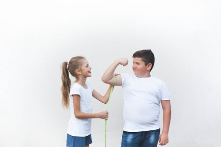 healthy slim little girl tease big fat boy measuring his muscle with tape copyspace Banque d'images