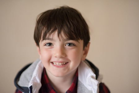 portrait of happy smiling cute little caucasian boy in hoodie and plaid shirt