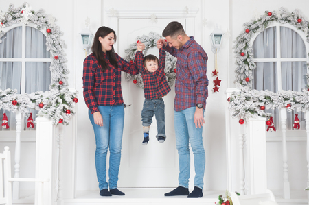 young mother and father raising child up standing on porch of white christmas house decoration