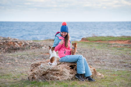 happy smiling beautiful girl in hat and track suit sitting on stone with two chihuahua small dogs near sea shore