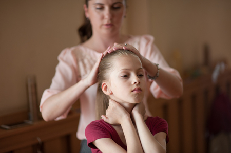 young beautiful caring mother fixing her dancer little thin daughters hair before concert show