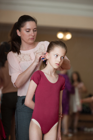 young caucasian mother corrects her ballerina dancer little slim daughters hair before show