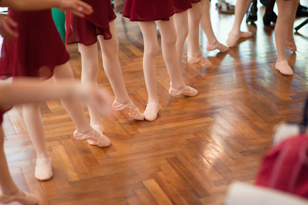 legs and feet of group of young ballerina girls on parquet in dance school indoors Stok Fotoğraf