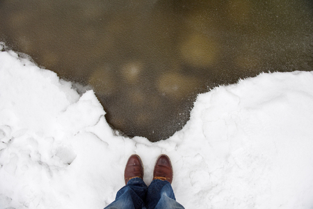 concept of cold winter man legs in jeans and feet in boots shoes standing on clean white snow before frozen water of river