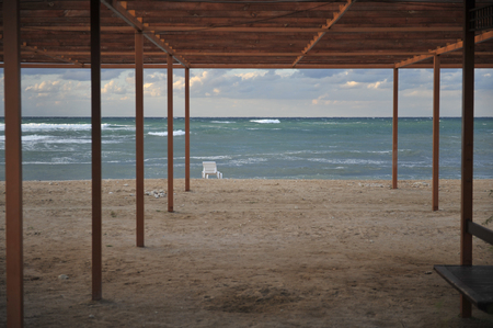 beautiful abandoned beach resort with wooden canopy tent and sunbed near stormy sea shore