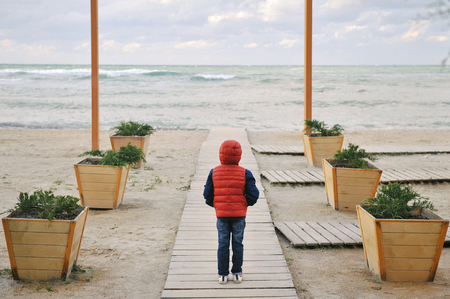 lonely little kid in red jacket with hood standing at deserted beach resort during off season dreaming concept