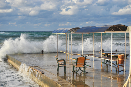 old rusty seats and tables of abandoned cafe on cold sea coast in off season with huge waves on stormy water