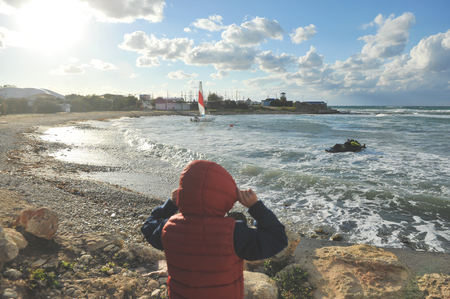 outdoor lifestyle concept photo little boy in hood and jacket looking at stormy sea coast with sailing yacht in early spring sunset Stok Fotoğraf
