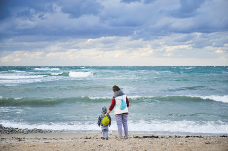 adult woman grandmother together with little kid in hood and jacket with backpack during travel near stormy cold spring sea