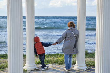adult woman holding hand of little kid in jacket standing among columns near storm sea outdoors Banque d'images