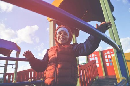 happy small kid in jacket and hood playing on playground in cold weather conditions outdoor leisure