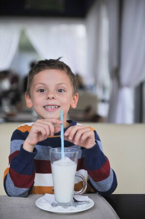 happy little boy with glass of milk shake with straw smiling indoors cafe