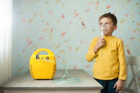 little caucasian boy making inhalation with nebulizer at home indoors Stok Fotoğraf
