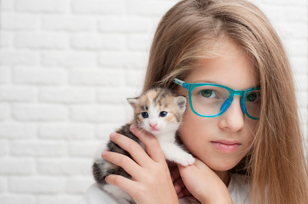 pretty little girl in glasses holding small kitty cat on her shoulder with copyspace