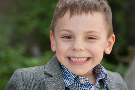 portrait of cute smiling little boy in shirt and jacket outdoors spring time