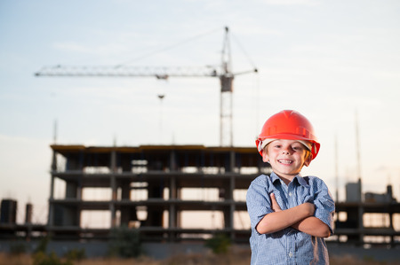 handsome happy smiling little kid in orange helmet and blue shirt standing on construction site with crane