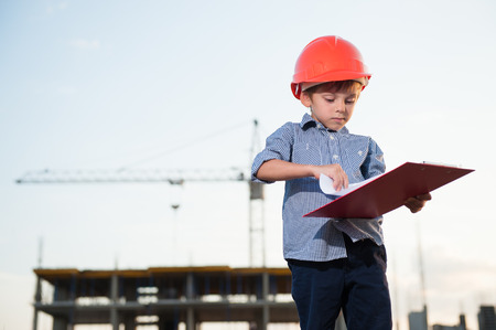 cute little boy in orange helmet with file with project sheets on construction site with crane Stok Fotoğraf - 122663674