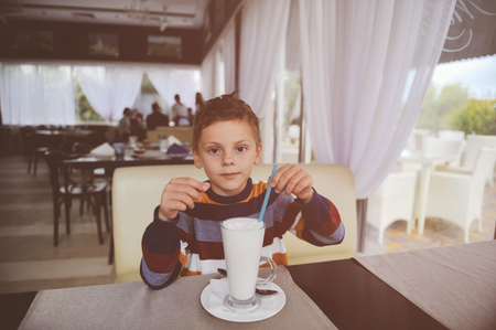 beautiful little boy in sweater sitting in restaurant with glass of milk shake Stok Fotoğraf