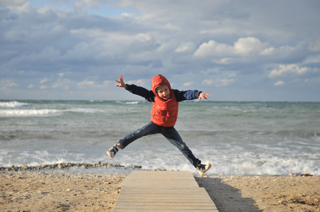 active little sport boy in jacket jumping high on spring sea shore background outdoors