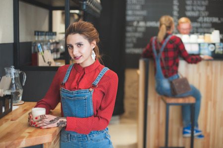 pretty young girl in fashionable denim suit with cup of espresso in coffee house with people