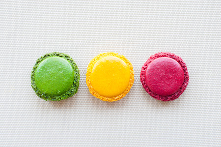 three colorful green yellow red french macaroons on table
