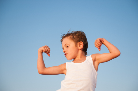 funny little kid showing his muscles on blue sky background with copy space