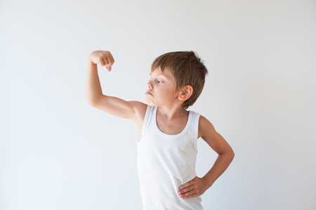 strong small child in tank top showing his muscle with grimace on his face
