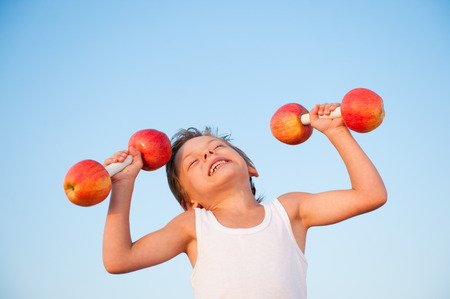 active strong little boy in tank top lifting apples dumbbells with effort on blue sky background Stok Fotoğraf