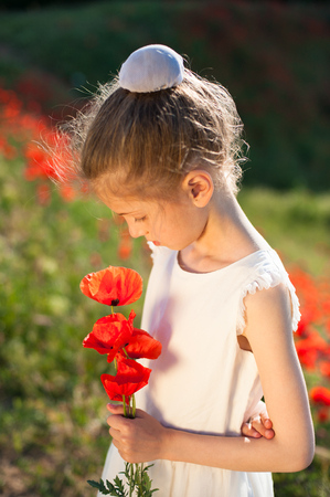 pensive little pretty girl with bouquet of poppy flowers
