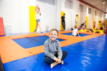happy smiling sitting little boy in trampoline hall with many children Stok Fotoğraf