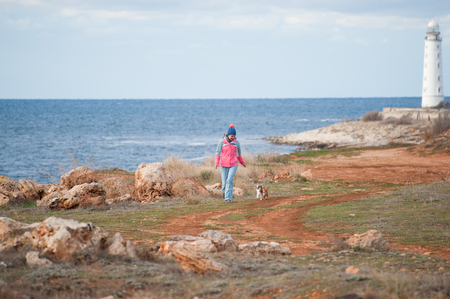 active young female in warmed track suit walking along sea coast with beacon with two little dogs Stok Fotoğraf