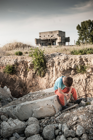 sad little boy refugee victim of war sitting upset on building ruins in military conflict zone in Syria