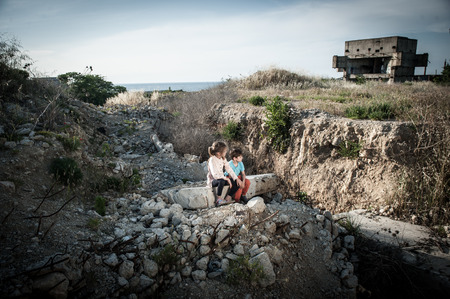poor kids orphans sitting on ruins of destroyed house in war conflict area at Middle East