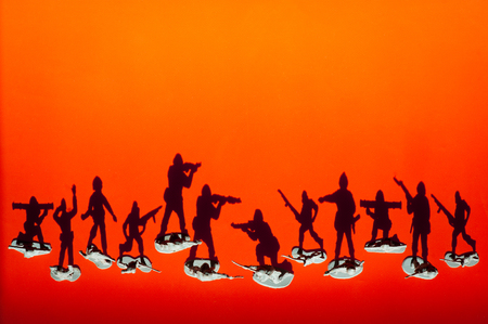 group of armed toy soldiers with shadows fighting each other on red orange sunset background Stok Fotoğraf - 116438061