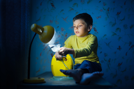 cute small child in yellow shirt sitting on table with lamp with water steam inhaler