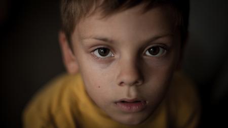 closeup portrait of cute face of afraid little boy