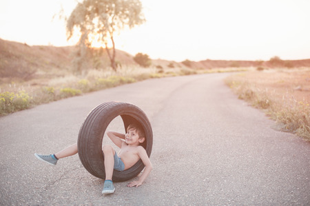 happy smiling small boy sitting inside car tire on empty highway road at summer sunset Stok Fotoğraf - 116438066