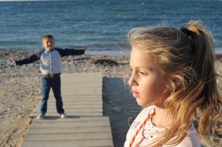 beautiful little girl face on foreground and small funny boy on background on beach in spring time Stok Fotoğraf - 116438071