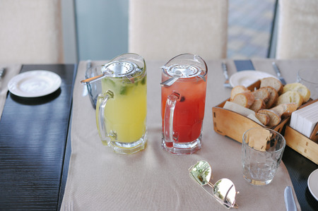 composition of two colorful glasses with tea sunglasses on table in restaurant Stok Fotoğraf - 116438074